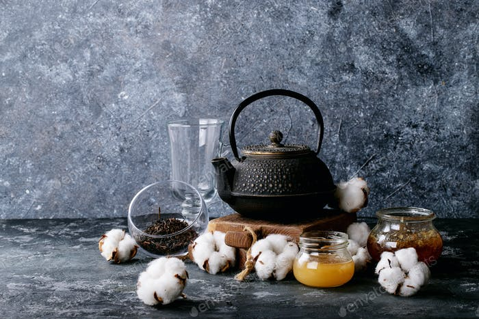 A black metal teapot and a cup of tea in glass cup