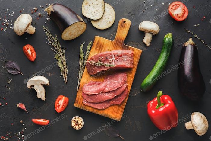 Raw beef filet mignon steaks on wooden board