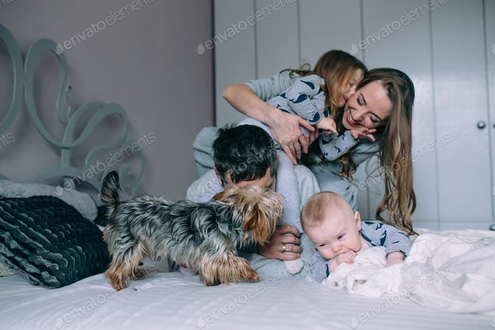 Family playing on bed in the bedroom