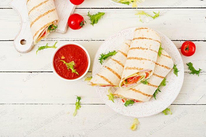 Tortilla Wrap mit Schinken, Käse und Tomaten auf einem weißen Holzhintergrund. Ansicht von oben