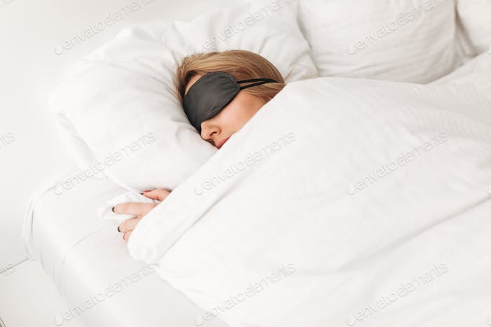 Lady wearing black eyes mask while sleeping in bed at home