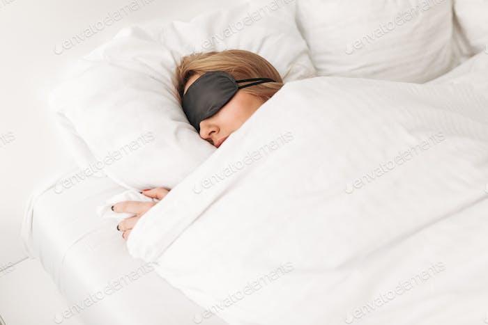 Señora con ojos negros máscara mientras duerme en la cama en Página de inicio