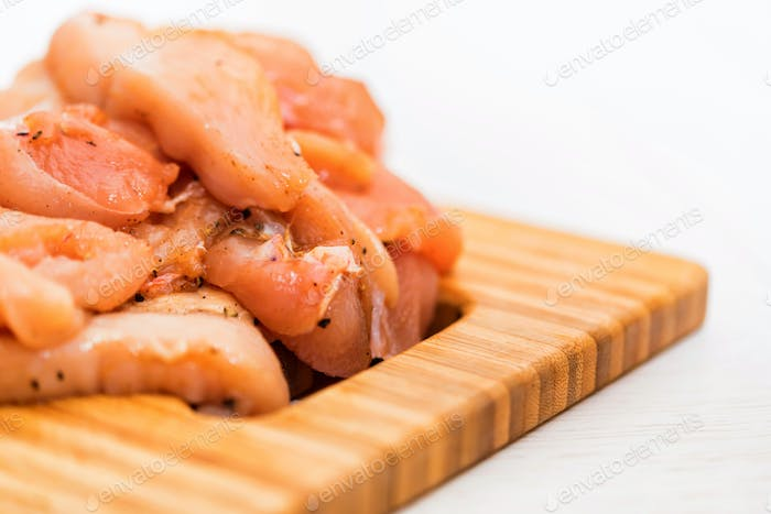 Raw chicken fillet with spices on wooden board