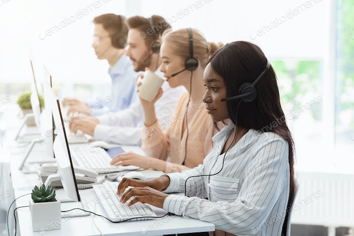 Line of call centre employees with headphones working on computers in open space office