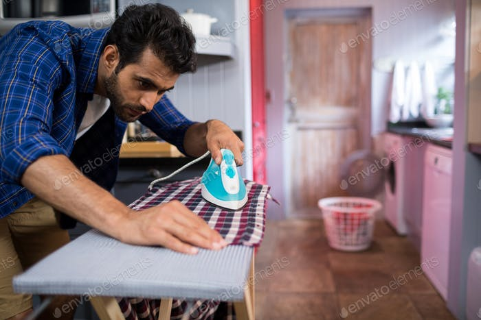 Young man ironing shirt