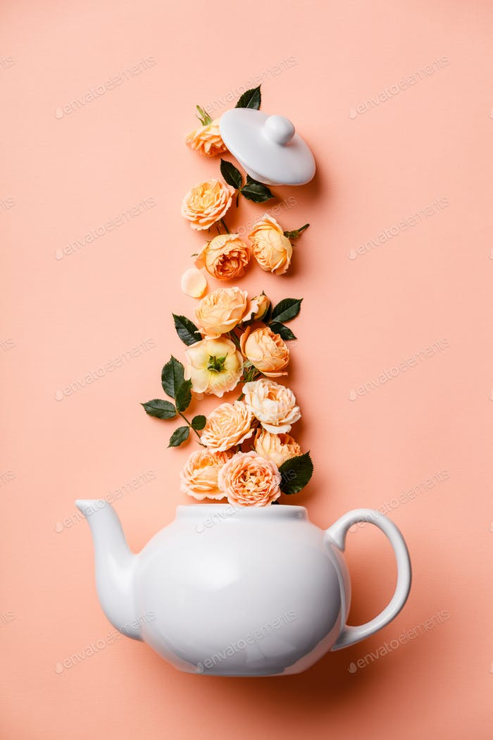 Creative layout made of whte tea pot with orange roses on pink background, flat lay