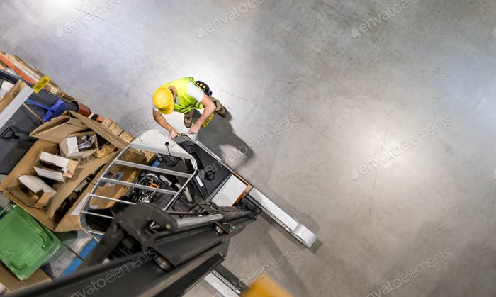 Mechanic repairs forklift in warehouse, view from above