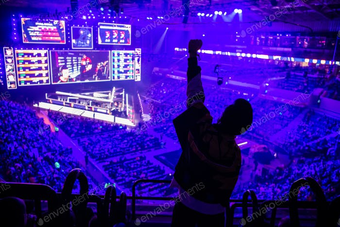 Großes eSports-Event. Video spiele Fan auf einer Tribüne in Turnierarena mit erhobenen Händen