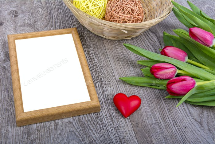 Picture frame, heart and tulips on a wooden desk