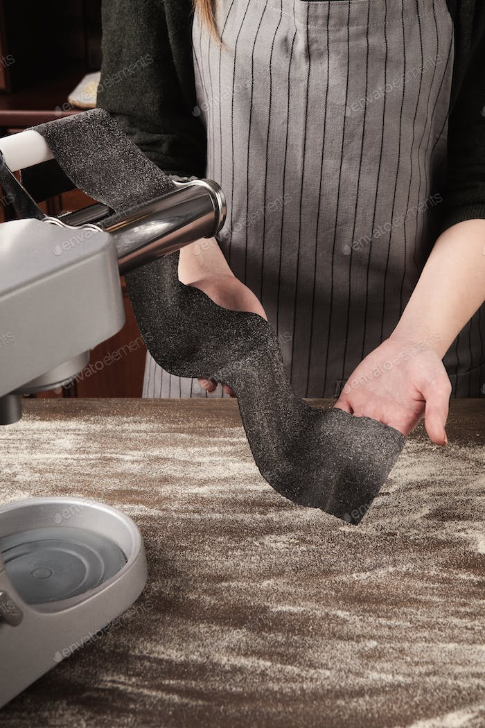 Rolling raw black dough with pasta machine