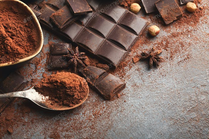Crushed chocolate bar pieces and cocoa on gray background
