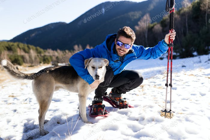 Handsome young man with his dog over winter background.
