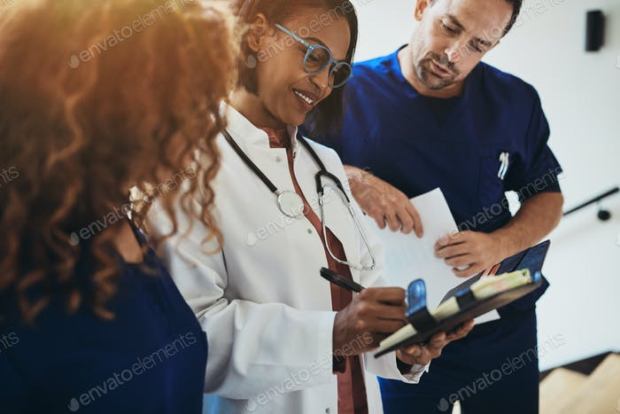 Smiling doctor talking with interns in a hospital corridor