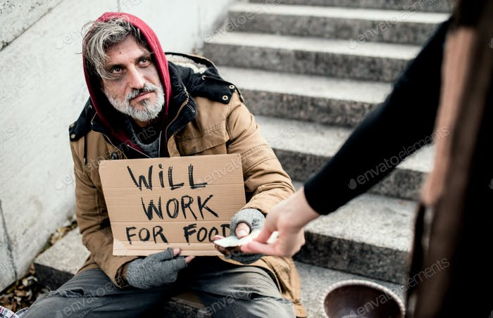 Unrecognizable woman giving money to homeless beggar man sitting in city.