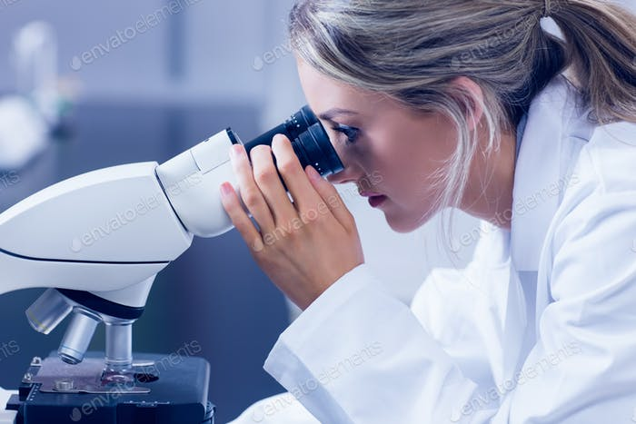 Science student looking through microscope in the lab at the university