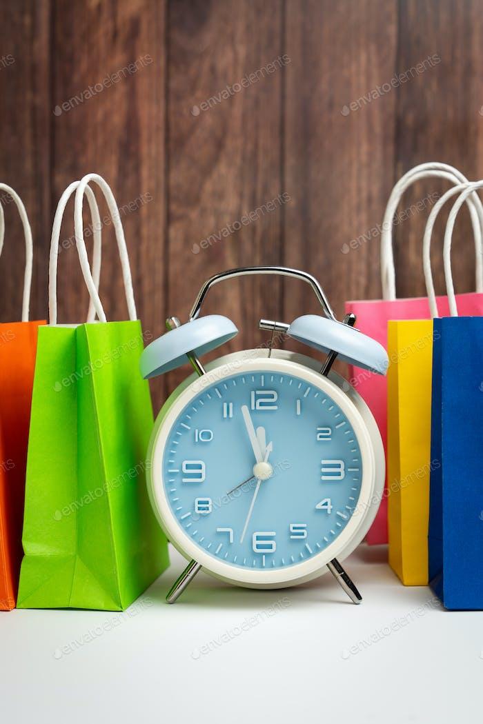 Wecker und bunte Einkaufstaschen