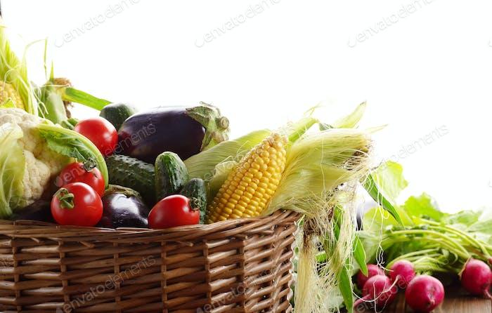 Organic vegetable food ingredients in the basket on white backgr