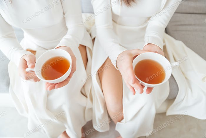 Two women in white dresses holding cups of tea