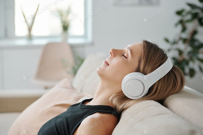 Side view of young relaxed woman in headphones lying on back of couch
