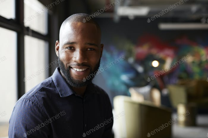Thumbnail for Mid adult black male creative in an office social area turning to camera smiling, close up
