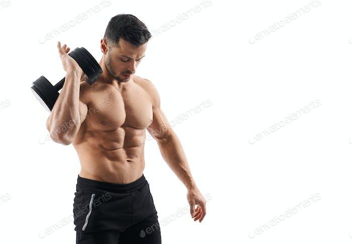 Shirtless bodybuilder holding dumbbell on shoulder