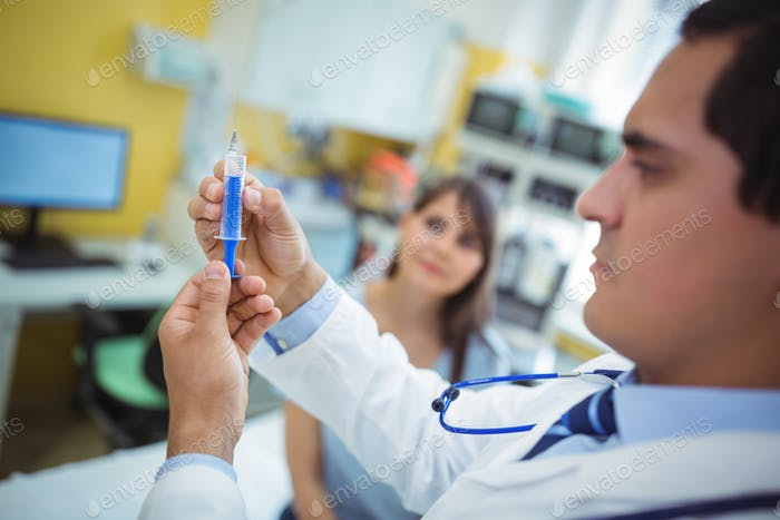 Doctor preparing a syringe to give an injection