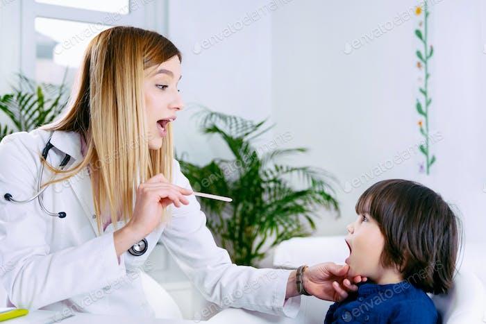 Pediatrician examining little boy's throat