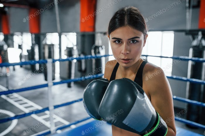 Young woman in sportive wear is in the boxing ring having exercise day