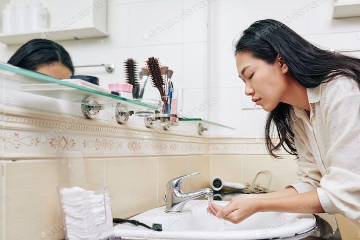 Junge Frau Gesicht waschen