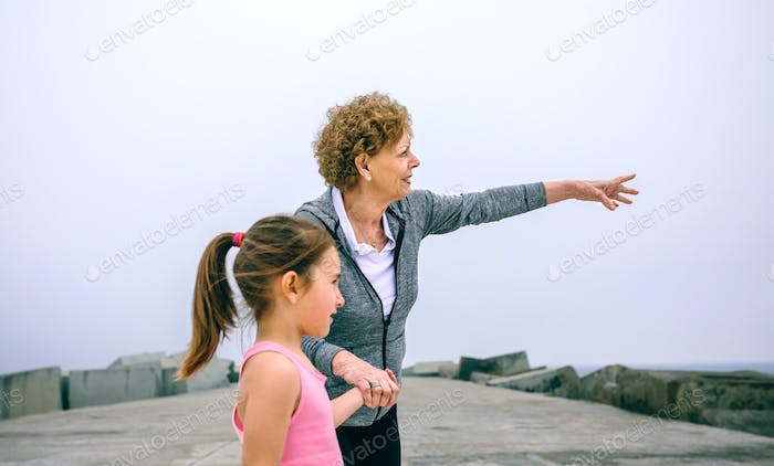 Senior sportswoman pointing with little girl