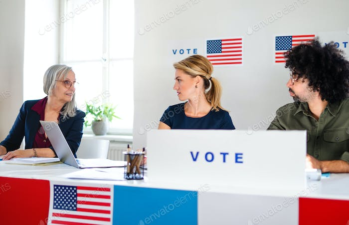 Members of electoral commission talking in polling place, usa elections