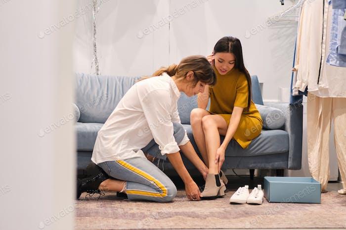 Joven consultor de moda cuidadosamente ayudando tratando en botas a atractiva chica asiática en showroom