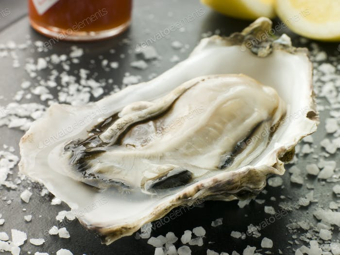 Opened Rock Oyster with Hot Chilli Sauce Lemon and Sea Salt