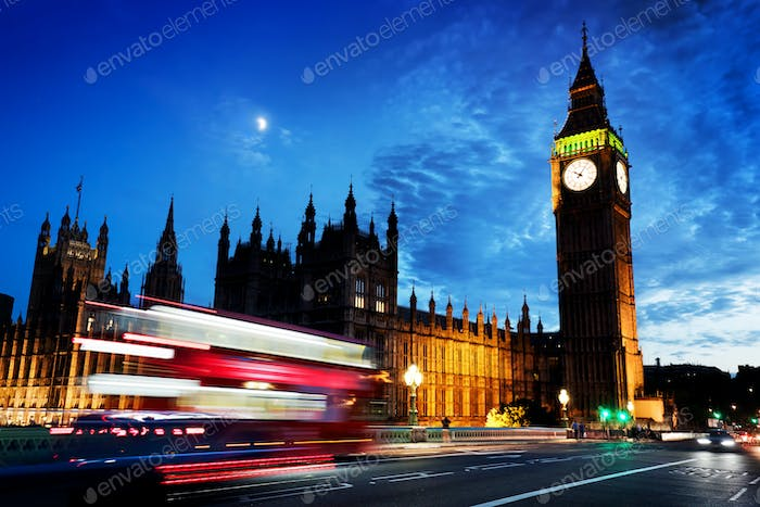 Red bus, Big Ben and Westminster Palace in London, the UK. at night. Moon shining