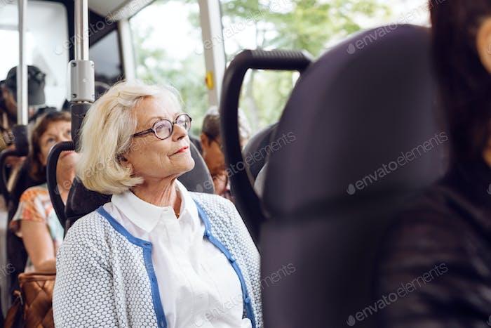 Senior woman sitting in bus
