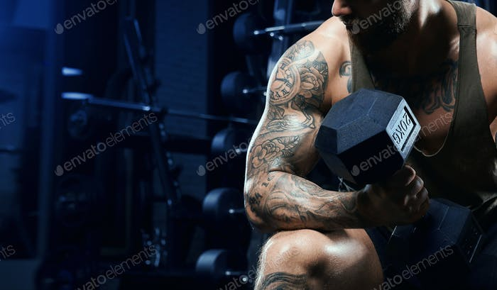 Male bodybuilder training biceps with dumbbell