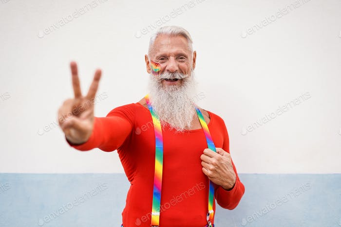 Cheerful hipster senior man at gay pride event doing peace gesture with hand