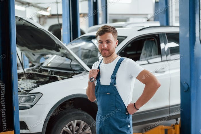 Positive emotions. Employee in the blue colored uniform works in the automobile salon