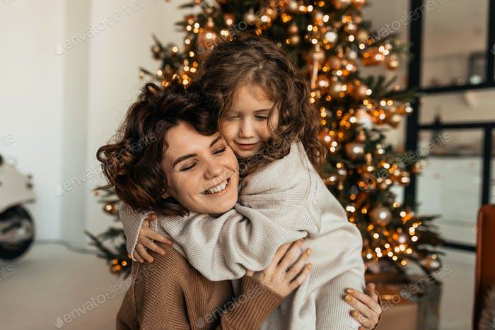 Charming lovable caucasian woman with curves hugging with her little daughter