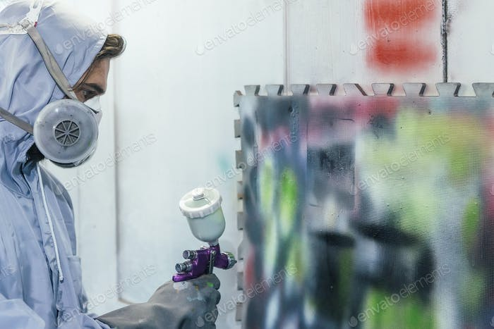 Man painting wall with different colors