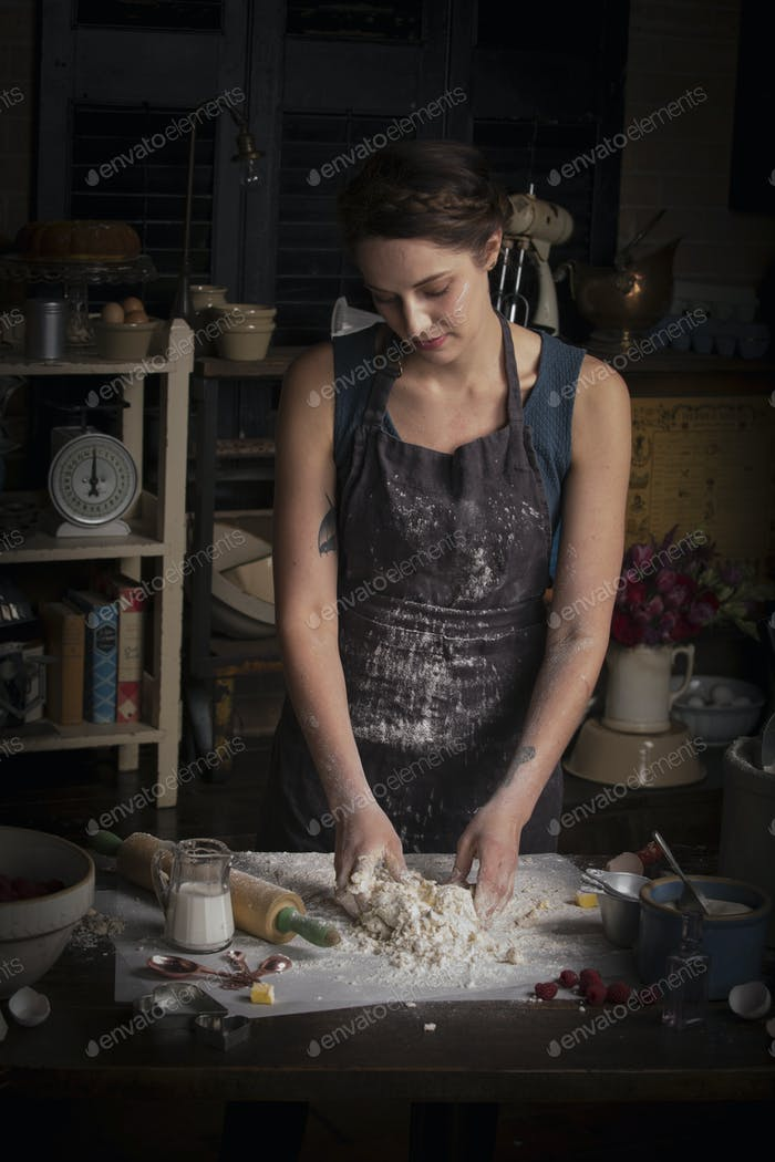 Valentine's Day baking, woman standing in a kitchen, preparing dough for biscuits.