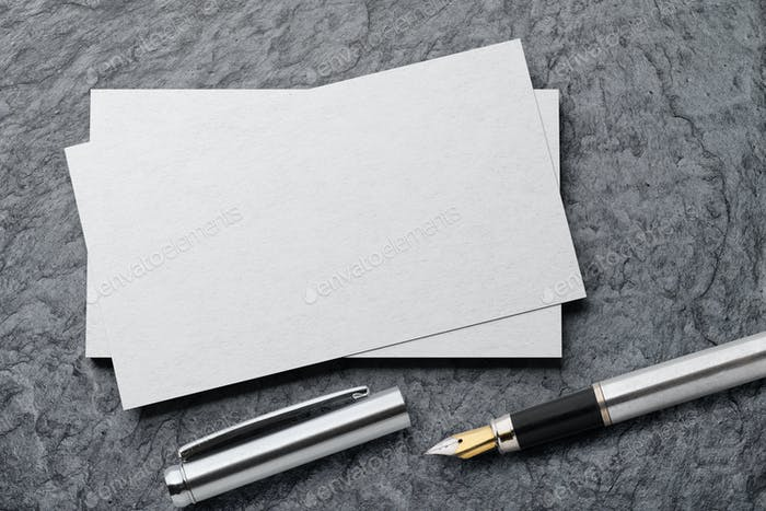 Mockup of business card with fountain pen at black slate background