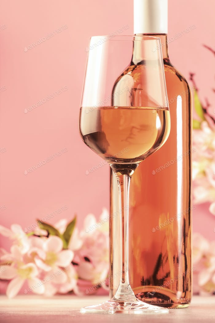 Rose wine glass with bottle and pink flowers. Rosado, rosato or blush wine