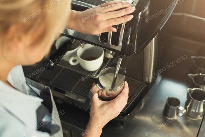 Experienced barista steaming milk in professional coffee machine