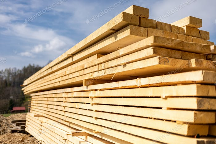 Stack of wooden beams on construction site prepared for building a house