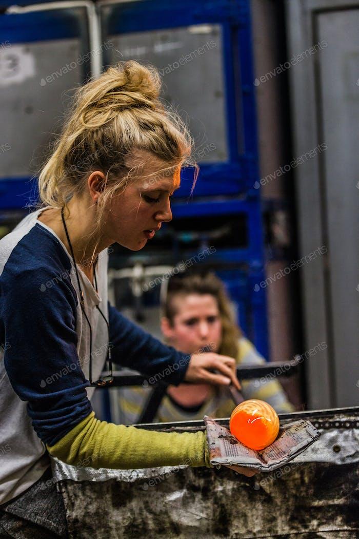 Zwei Frauen Shaping Glas auf der Blowpipe