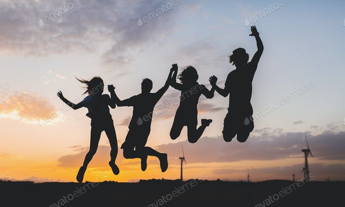 friends company silhouettes on sunset desert landscape jumping together
