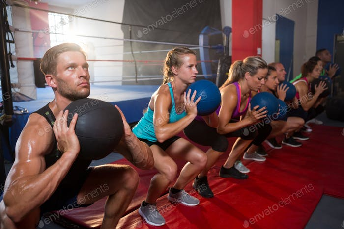 Group of young athletes exercising with balls