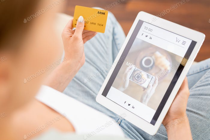 Contemporary consumer with plastic card and tablet looking through online goods