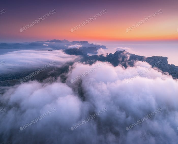 Thumbnail for Aerial view of low clouds, mountains, sea and colorful sky at sunset.